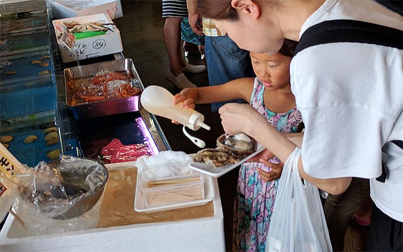 万代島鮮魚センター-岩カキを食べる様子