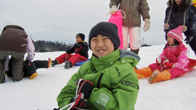 スキーこどもの日にソリを楽しむ子供達